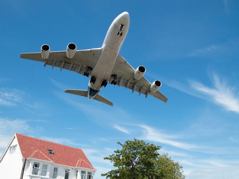 Flugzeug fliegt über einem Einfamilienhaus mit eingebautem Schallschutz Isolierglas am Himmel hinweg