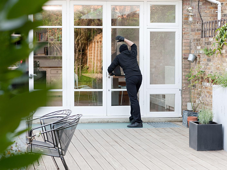 Einbrecher schaut zur Terrassentür ins Haus rein
