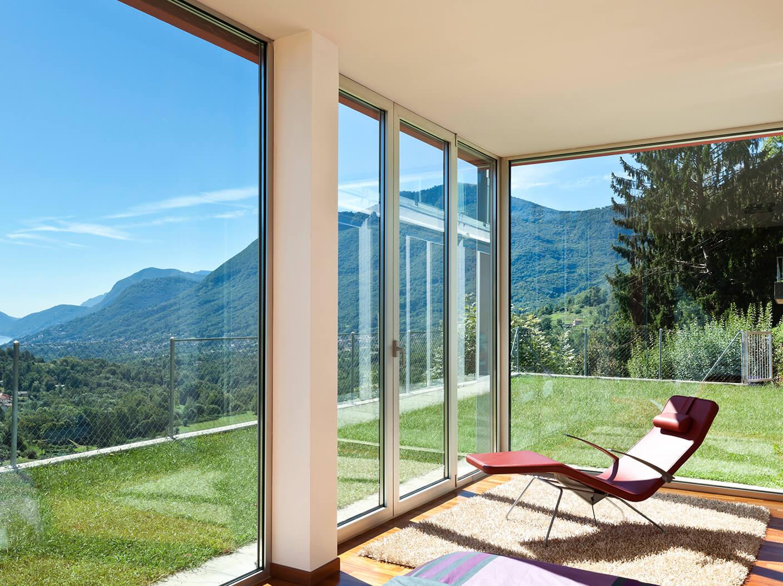 Bild eines Zimmers mit einem Liegestuhl von Innen, in das viel Sonne scheint