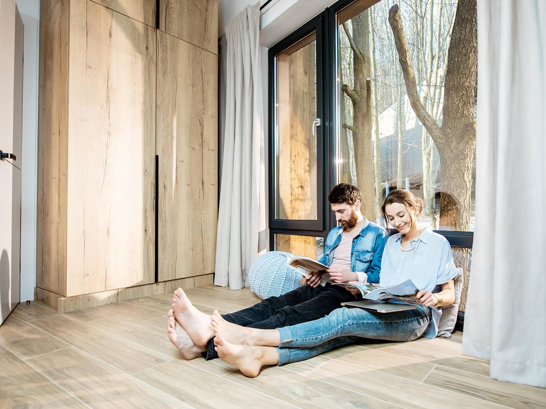 Paar sitzt auf dem Boden, an ein bodentiefes Fenster gelehnt und ließt Zeitung